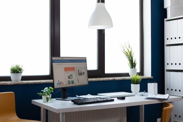 Fiori che circondano il computer con statistiche finanziarie e grafici in uno spazio elegante ufficio vuoto in c...