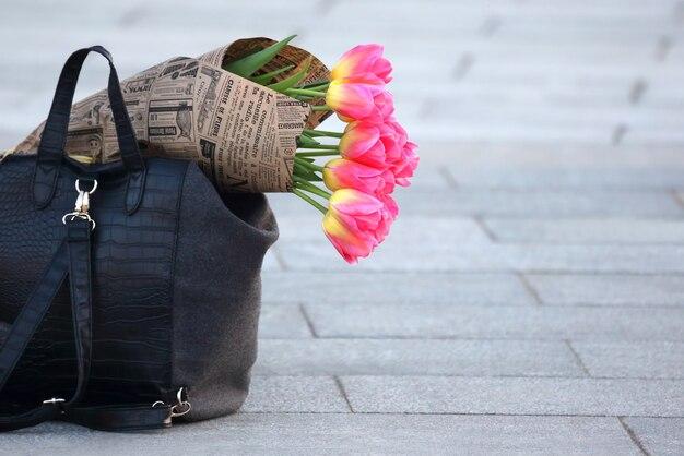 Tulipani di fiori avvolti nel giornale che giace nella borsa delle donne