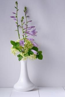 Fiori in un vaso su un tavolo di legno bianco. mattina, natura morta rustica.