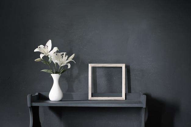 Fiori in vaso e cornice in legno su sfondo scuro muro