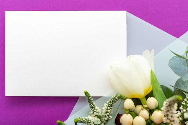Invito a nozze fiori. biglietto di congratulazioni in bouquet di tulipani fiori bianchi, eucalipto su sfondo viola.