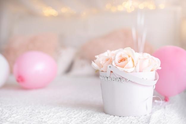 Fiori in scatola bianca e palloncini sul letto. regalo per la festa della mamma
