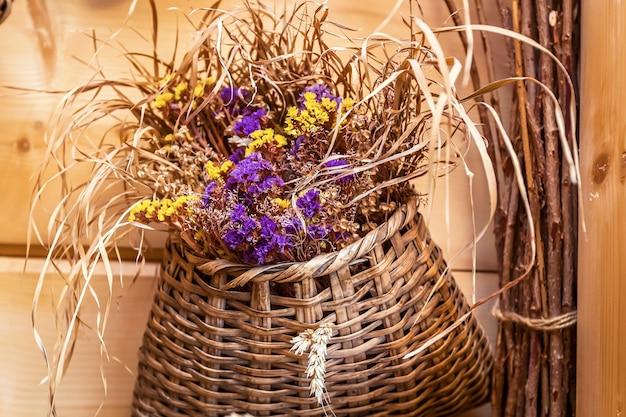Fiori in un cesto di vimini sullo sfondo di una parete in legno. fiori in un cesto di vimini