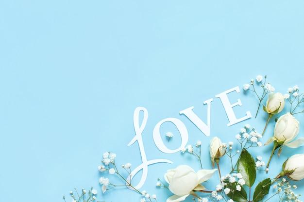 Fiori e parola amore su fondo azzurro