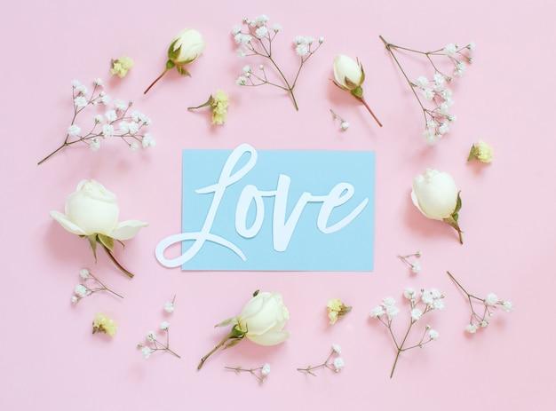 Fiori e parola amore su uno sfondo rosa chiaro vista dall'alto
