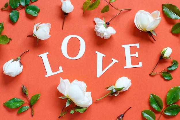 Fiori e parola amore su una vista dall'alto di sfondo rosso