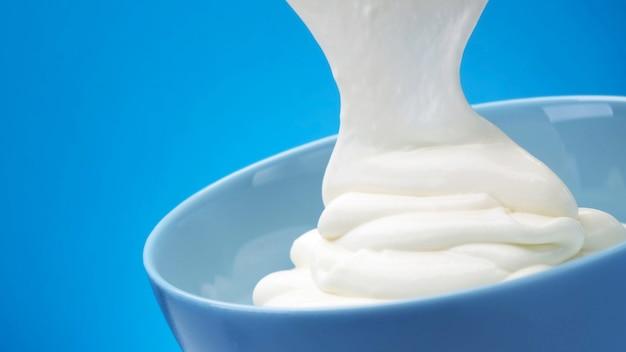 Yogurt greco fresco che scorre su sfondo blu, panna acida montata