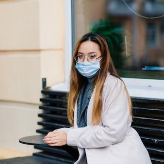 Maschera di protezione contro la diffusione del virus dell'influenza protettiva contro virus e malattie influenzali donna asiatica che indossa mascherina chirurgica sul viso negli spazi pubblici. assistenza sanitaria.