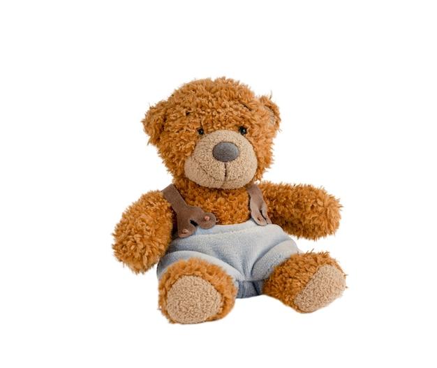 Regalo marrone lanuginoso del giocattolo dell'orsacchiotto che porta i pantaloni blu dell'imbracatura isolati