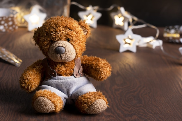 Giocattolo lanuginoso marrone dell'orsacchiotto che porta i pantaloni blu sulla tavola di legno contro le decorazioni di natale
