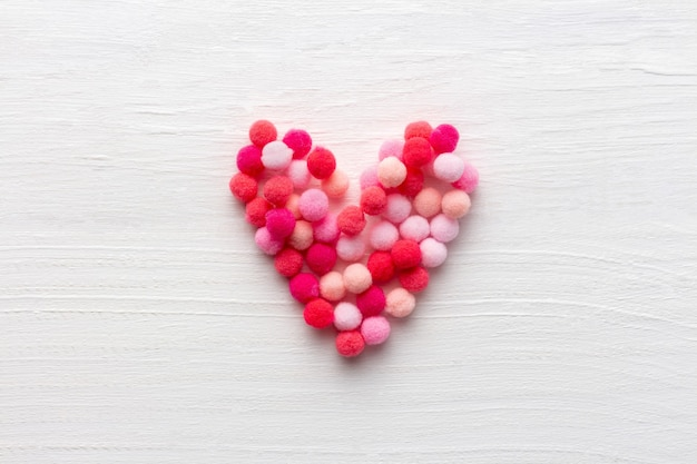 Cuore soffice come simbolo di amore su fondo di legno bianco per la festa della mamma o il giorno di san valentino