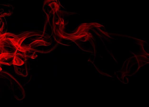 Soffici sbuffi di fumo rosso e nebbia su sfondo nero, design del fuoco