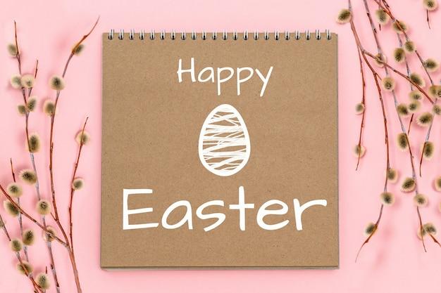 Soffici rami di salice figa e blocco note di carta artigianale, uovo bianco carino disegnato, buona pasqua, vacanza primaverile domenica delle palme
