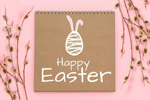 Soffici rami di salice e blocco note di carta artigianale con coniglietto, uovo con orecchie carine, buona pasqua, festa di aprile domenica delle palme, primavera