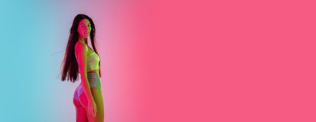 Volantino. bella ragazza seducente in costume da bagno alla moda su sfondo rosa-blu sfumato alla luce al neon. ritratto a figura intera. copyspace per l'annuncio. estate, moda, bellezza, concetto di emozioni.