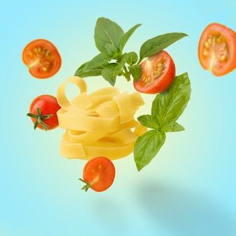 In volo, fettuccine crude con pomodorini e foglie di basilico. isolato colorato.