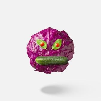 Faccia arrabbiata volante fatta da cavolo rosso di verdure fresche naturali fresche, bocca di cetriolo e occhi di pomodorini sopra sfondo con ombre morbide, spazio di copia concetto vegano.