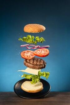Hamburger volante su base in legno su blu