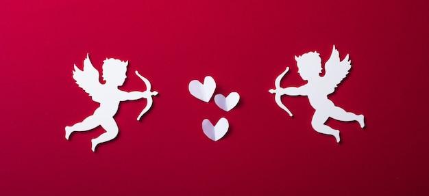 Sagoma di cupido volante, striscioni di san valentino felice, stile di arte della carta. amour su carta rossa
