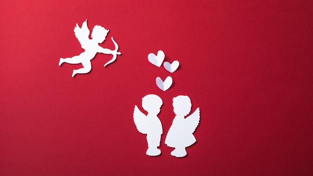 Sagoma di cupido volante, due angeli bianchi, striscioni di san valentino felice, stile di arte della carta. amour su carta rossa