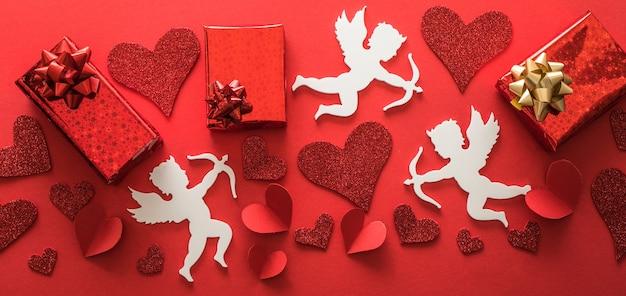 Sagoma di cupido volante con cuori, regali, striscioni di san valentino felice, stile di arte della carta. amour su carta rossa