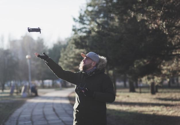 Il drone volante atterra sulla mano di un uomo con un telecomando