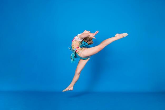 Una ginnasta volante esegue un esercizio su una parete isolata blu