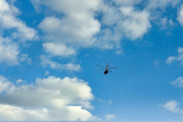 Elicottero volante sullo sfondo di nuvole e cielo blu. piccoli aerei