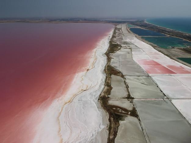 Volando sopra un lago salato rosa sale di produzione di sale di evaporazione salina campi di stagno nel salato