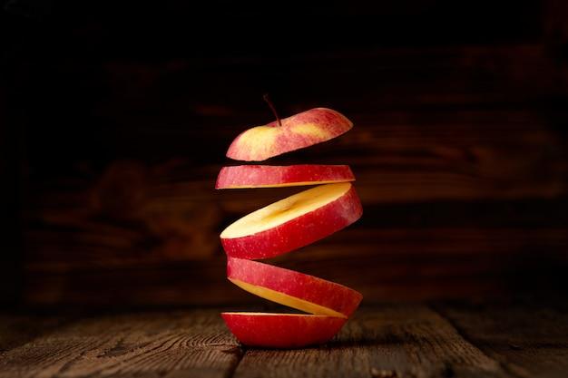 Fette volanti di mela rossa su un fondo di legno rustico.