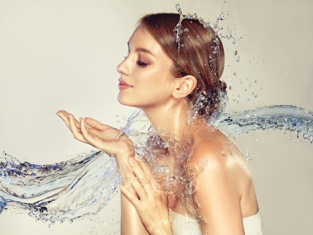 Spruzzi volanti di acqua blu pulita toccano il collo e il corpo delle mani