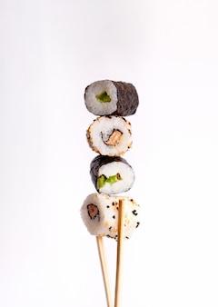 Sushi volante su sfondo bianco, gustosi rotoli di sushi, avocado e bacchette