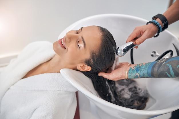 Schiuma che scorre lungo i capelli scuri puliti