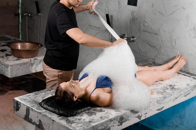 Peeling con schiuma nella spa. la donna è sdraiata sulla schiena e si rilassa. procedura dell'hammam turco.