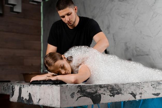 Peeling con schiuma nell'hammam della spa turca. il modello attraente è rilassante nella spa. il massaggiatore sta facendo il massaggio usando il guanto di spugna.