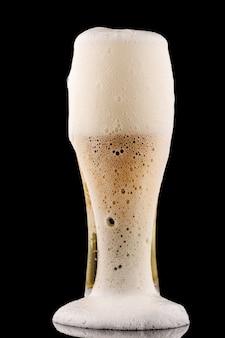 La schiuma si riversa da un bicchiere di birra