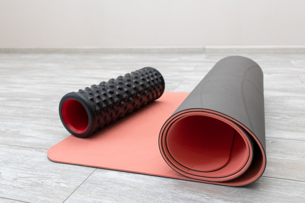 Rullo di schiuma e tappetino da yoga in soggiorno per lo yoga