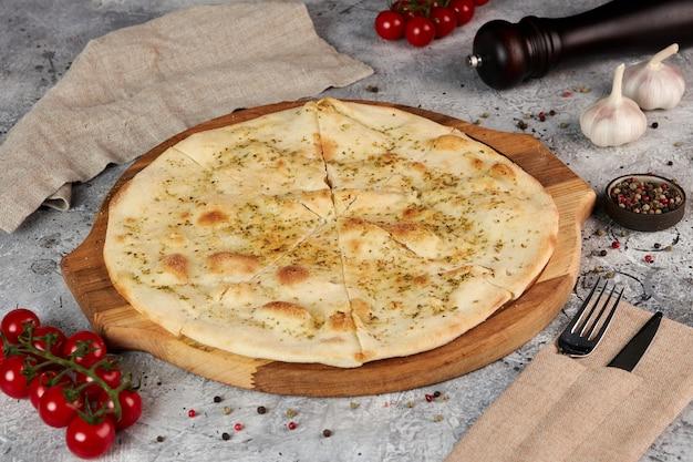 Focaccia con aglio e origano su una tavola di legno, sfondo grigio