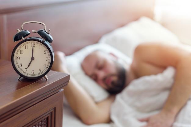 Concentrarsi sulla sveglia, l'uomo si sveglia presto la mattina, il concetto di sonno sano, effetto rumoroso per l'atmosfera
