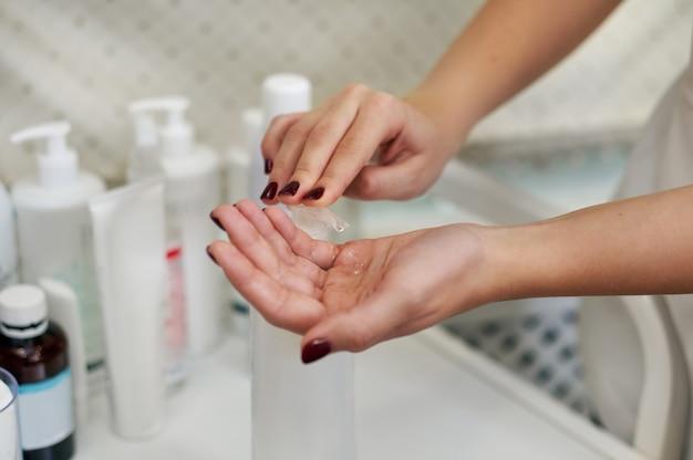 Concentrati sulle mani dell'estetista mentre applichi il gel disinfettante sulle mani utilizzando un erogatore