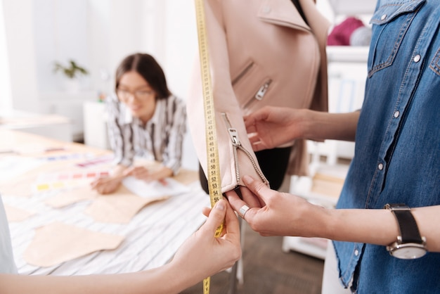 L'attenzione si concentra su due paia di mani femminili delicate e pulite, un paio delle quali tiene una manica di una giacca rosa mentre l'altra misura la lunghezza della manica con un nastro