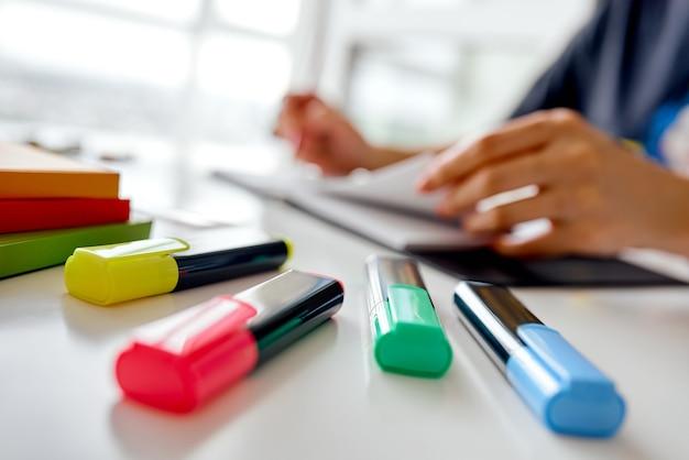 Concentrati sul creatore di testo colorato e sulle mani sfocate con il taccuino aperto. foto di alta qualità