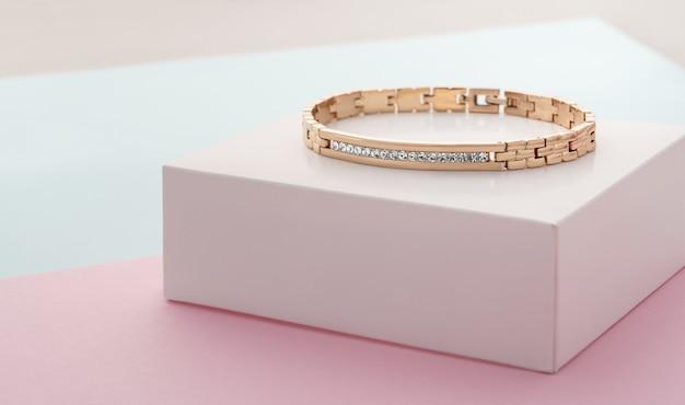 Concentrati sui diamanti sul braccialetto d'oro su sfondo di colori pastello con spazio di copia