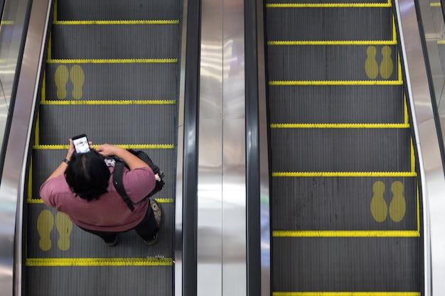 Concentrarsi sulla scala mobile dalla vista dall'alto nella fase di quarantena della vita moderna
