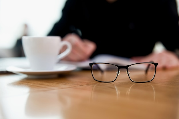 Focus su occhiali sul tavolo. uomo concentrato sfocato che scrive qualcosa nella sua agenda. tazza di buonissimo piatto bianco. tavolo di legno. atmosfera accogliente da caffetteria. lavoro a distanza.