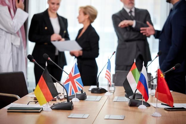 Concentrarsi sulla bandiera di diversi paesi durante un incontro di lavoro o politico, diversi partner parlano, discutono strategie e idee all'ordine del giorno