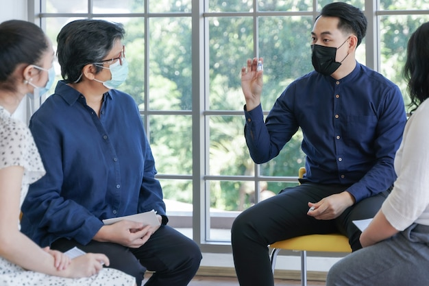 Focus group sulla salute mentale da parte di un consulente psicologo di persone asiatiche con riunione di maschere per il viso