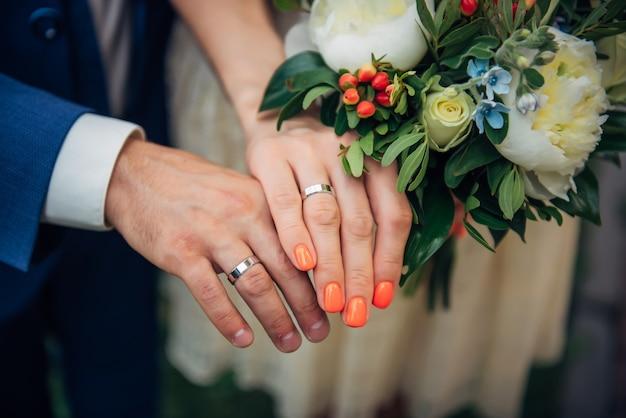 Concentrarsi sulle mani della sposa e dello sposo, bouquet da sposa, vista dall'alto