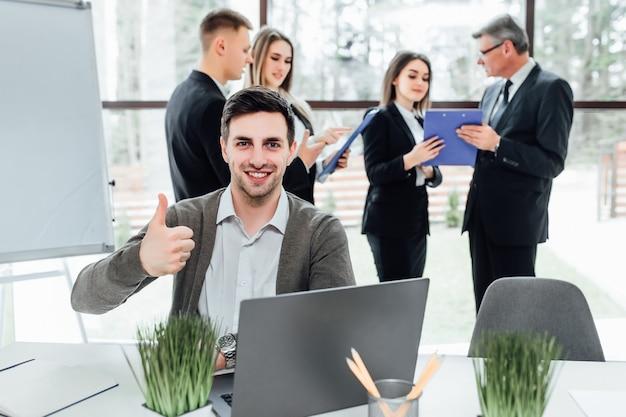 Concentrarsi su un bell'uomo d'affari alza il dito in un ufficio moderno.