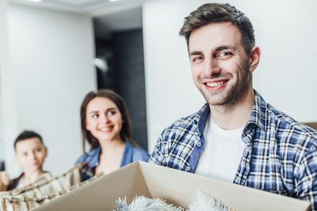 Concentrati sul padre felice che tiene in mano le scatole con le cose in un nuovo appartamento